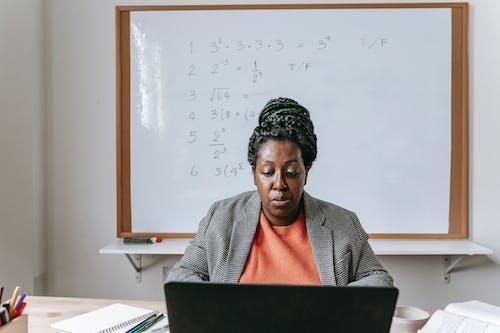 Serious black teacher giving mathematics online on laptop