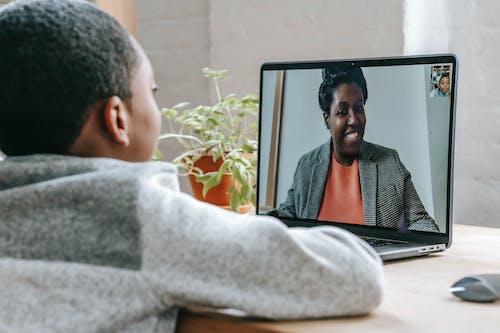 Black boy talking with teacher about school online