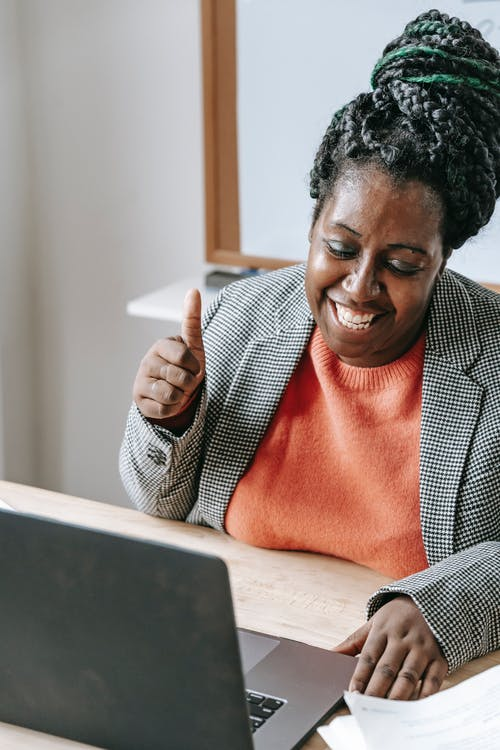 Glad black woman having video call and showing thumb up