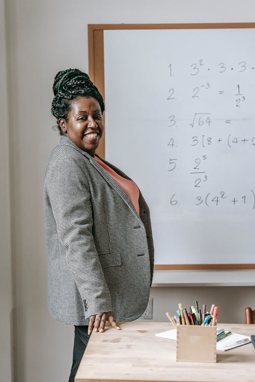 Cheerful black woman preparing for lesson in classroom