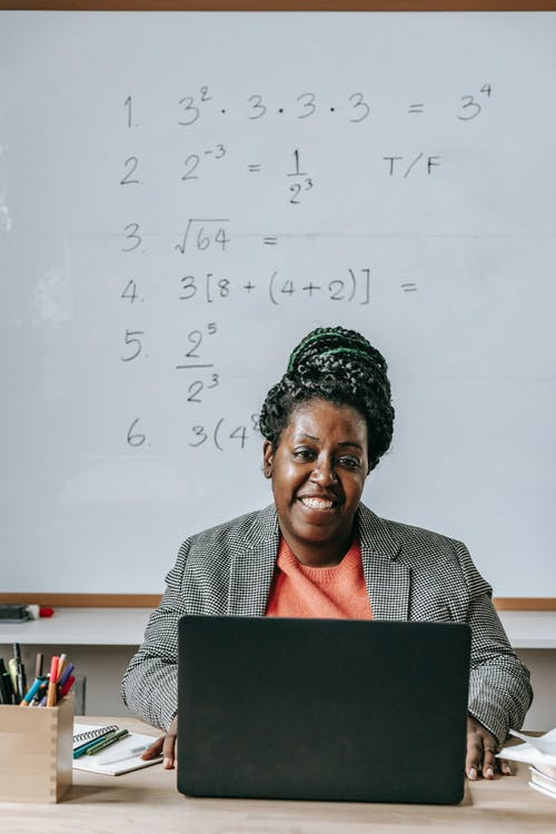 Cheerful African American female using netbook and smiling while looking at camera in classroom with whiteboard