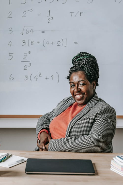 Delighted black woman with toothy smile in classroom