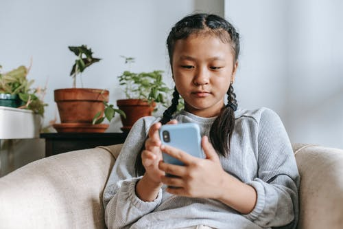 Concentrated Asian girl text messaging on smartphone while sitting on comfy armchair at home