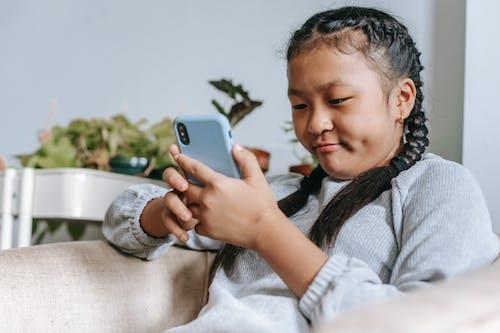 Fille Asiatique Concentrée Regardant Smartphone
