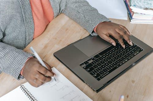 Crop black woman using laptop and writing