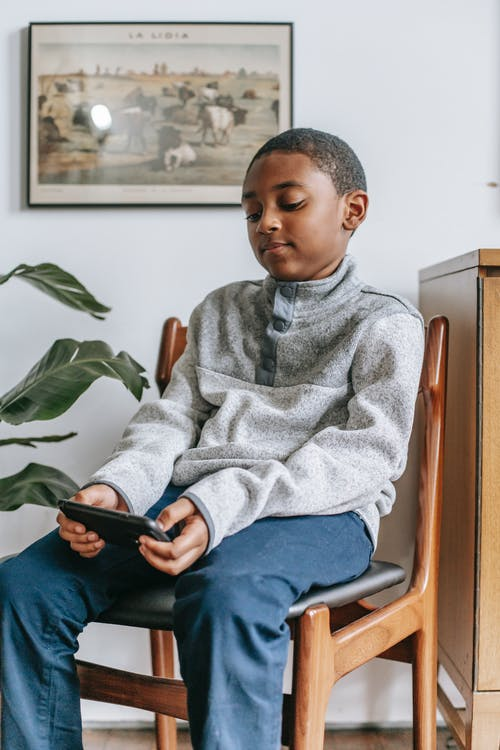 Focused black boy with smartphone