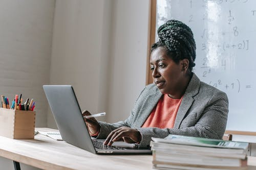 Black woman at table with laptop