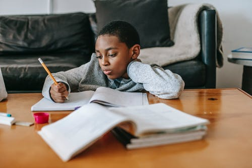 Focused African American boy writing in copybook with pencil while doing homework at wooden table