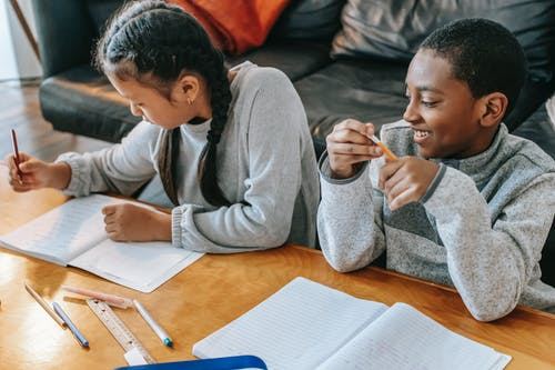 Positive African American boy looking at focused Asian girl while doing homework together at wooden table