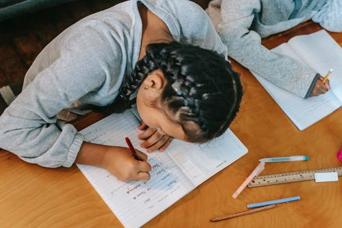 Children writing in copybooks at table
