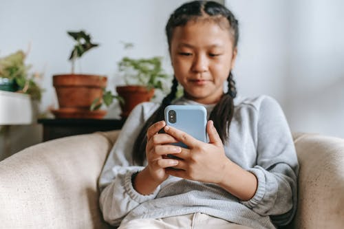 Serious ethnic girl with smartphone