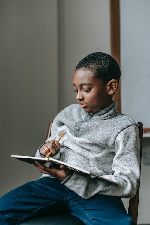 Focused black boy writing in notebook