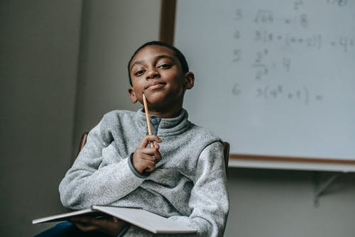Thoughtful black boy with pencil
