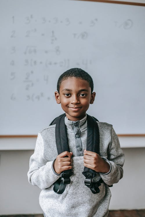 Cheerful African American boy in casual outfit with backpack standing against whiteboard in classroom and looking at camera