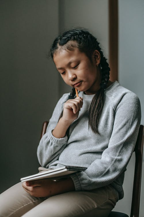 Pensive ethnic girl with copybook