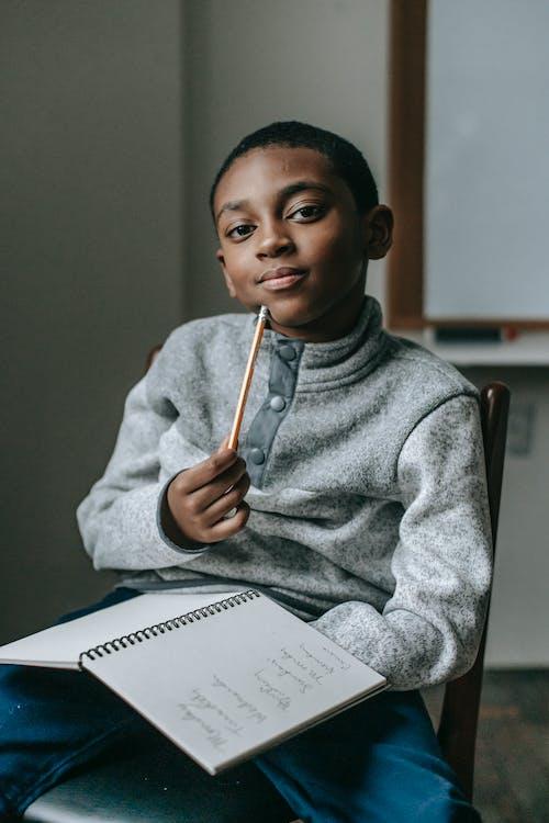 Criança Séria E étnica Com Lápis E Caderno