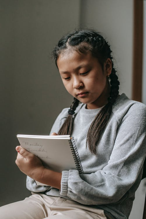Focused Asian girl writing in notebook while doing task at school sitting on chair