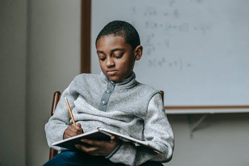 Concentrated African American boy doing tasks in copybook while sitting on wooden chair in classroom