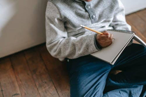 From above faceless child with pencil and notebook taking notes while sitting on floor