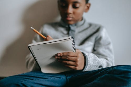 Focused black kid writing in notebook