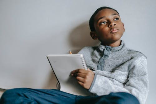 Little thoughtful black kid sitting on floor with notebook and pencil looking away against white wall