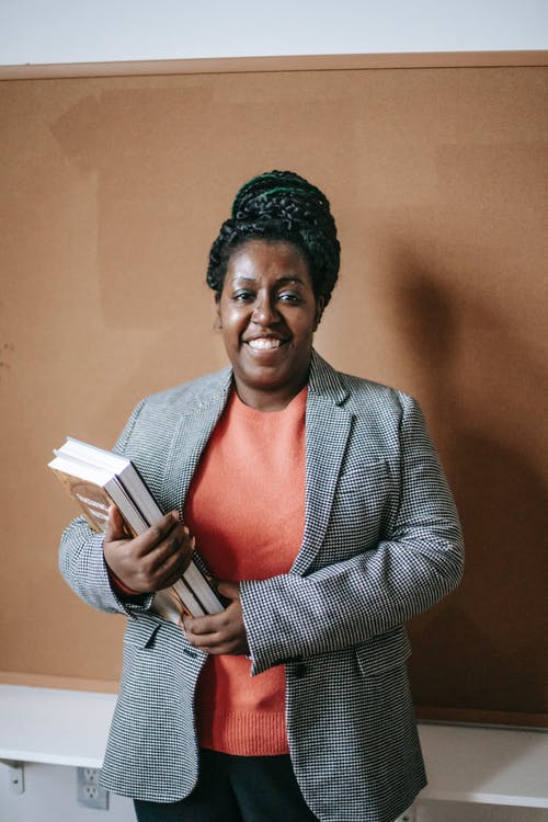 Cheerful adult black woman in jacket holding pile of books standing in classroom and looking at camera
