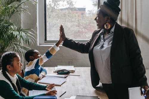 Side view of smiling black boy giving high five to teacher while sitting with diverse classmate girl at desk in classroom