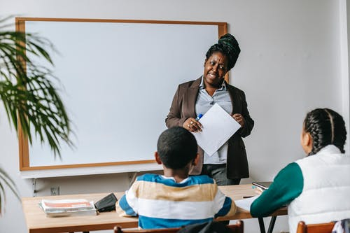 Black teacher with kids in modern classroom