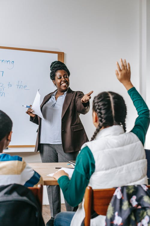 Black teacher answering questions of pupil