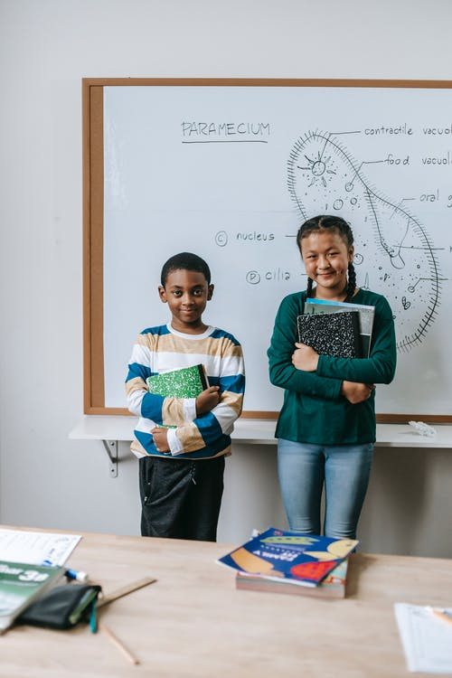Cheerful multiracial schoolkids with notepads at whiteboard