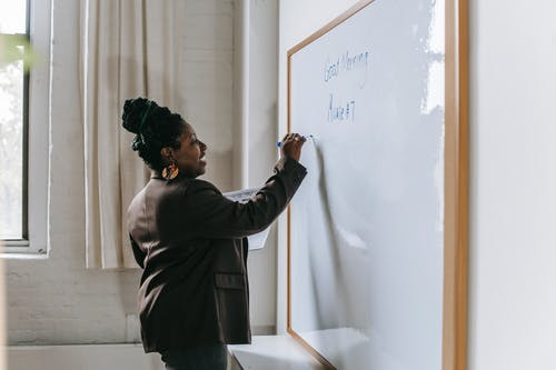 Side view of smiling African American woman writing on whiteboard standing in modern school classroom