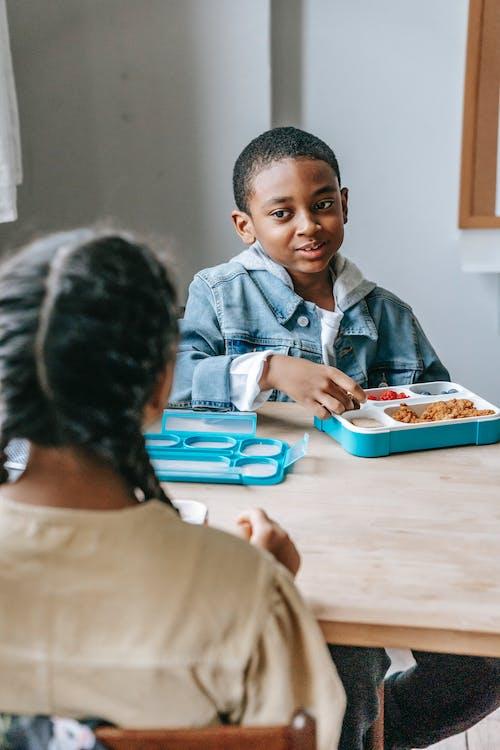 Anak Sekolah Kulit Hitam Dengan Kotak Makan Siang Berbicara Dengan Teman Sekelas Etnik Tanaman