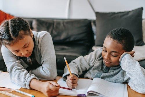 Anak Sekolah Multietnis Dengan Buku Kerja Berinteraksi Saat Belajar Di Rumah