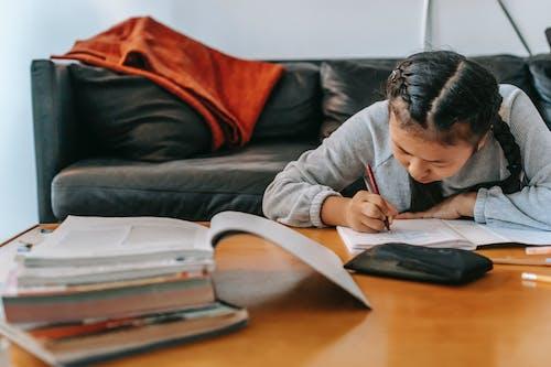 Diligent ethnic schoolgirl taking notes in copybook at desk