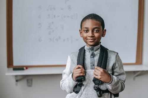 Smiling black schoolboy near white board in classroom