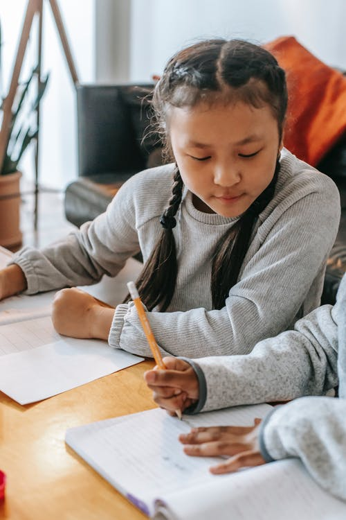 Crop anonymous ethnic schoolchild writing in copybook near attentive girl while doing homework at home