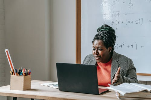 African American female teacher talking during class on netbook while sitting at desk with books and stationery in classroom