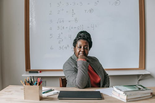 African American female teacher in formal clothes sitting at table with books and laptop and looking at camera