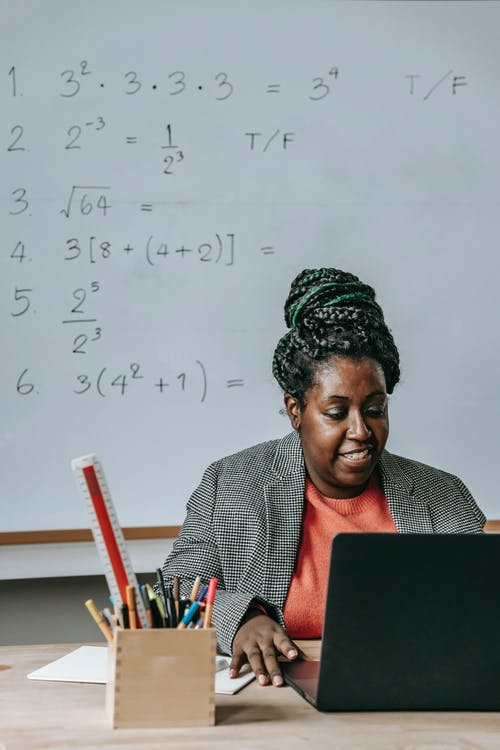 African American female teacher in formal clothes sitting at table with netbook and office supplies and looking at screen