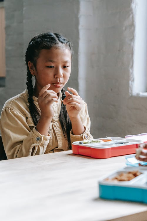 Asian schoolgirl sitting at table and eating snacks from container