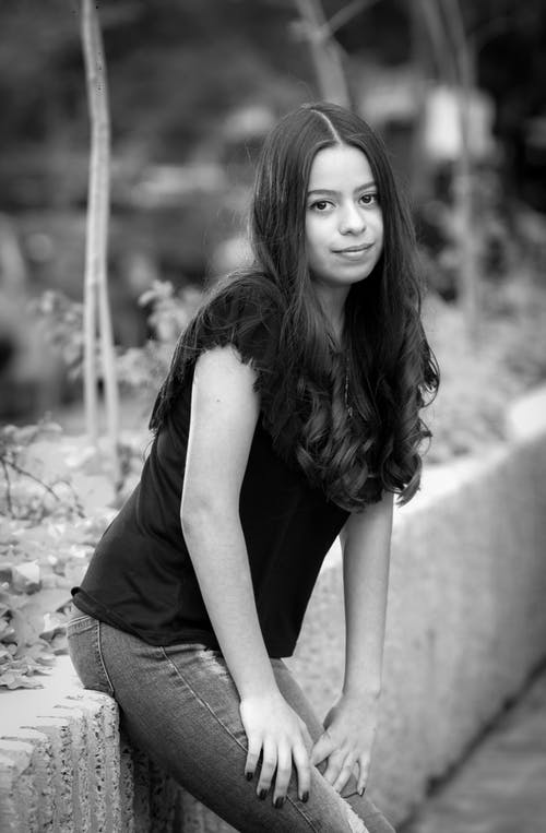 Grayscale Photo of a Girl Looking at the Camera while Sitting