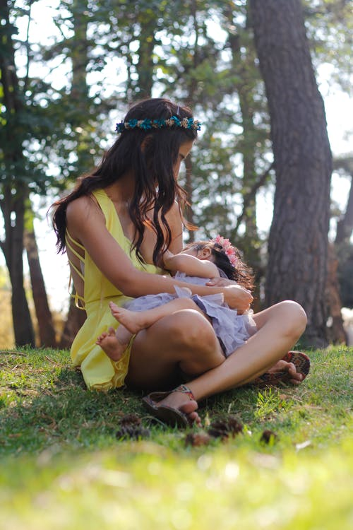 Mother Breastfeeding her Child while Sitting on Grass
