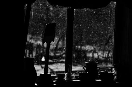 Black and white of jugs with cup and pan against window in aged building in countryside