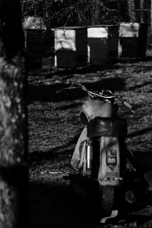 Old motorcycle near rough fence in countryside