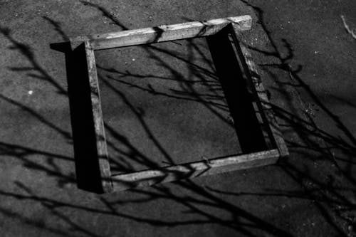 From above black and white of aged square shaped frame on walkway with tree twigs shade