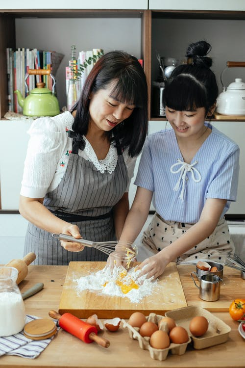 Delightful Asian woman and daughter mixing ingredients for dough together in kitchen