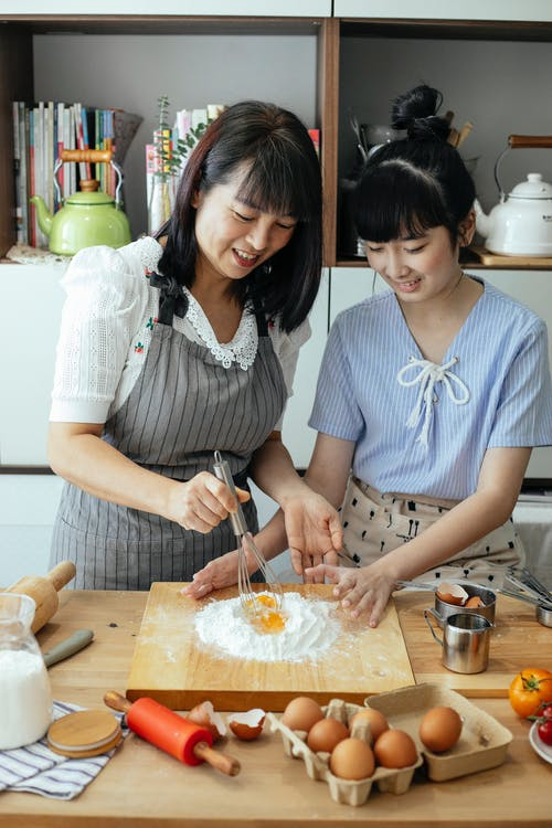 Cheerful Asian mother and daughter kneading pastry with whisk in kitchen