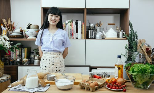 Happy young Asian woman standing near table with ingredients for dough