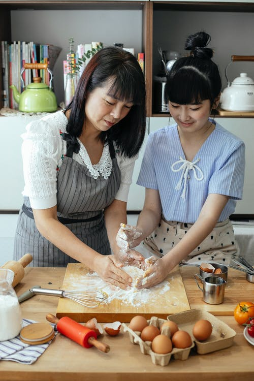 Focused Asian woman and girl kneading dough together in kitchen