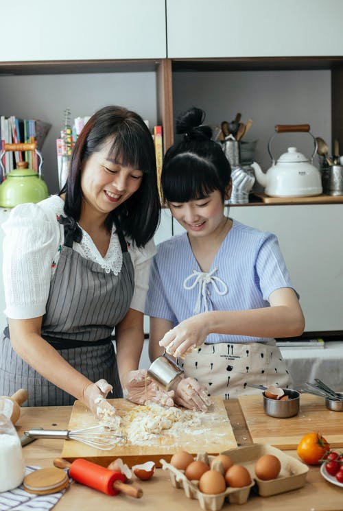 Smiling Asian mother and daughter making dough together in kitchen